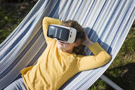 Girl lying in hammock in garden wearing VR glasses - MOEF02274
