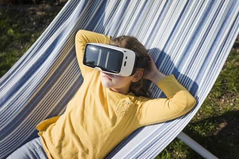 Girl lying in hammock in garden wearing VR glasses - MOEF02274