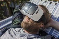 Man lying in hammock in garden wearing VR glasses - MOEF02277