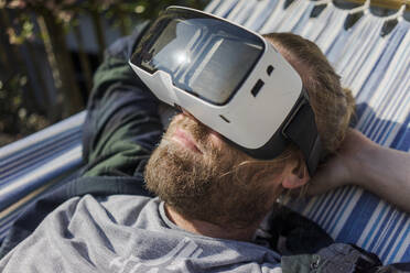 Man lying in hammock in garden wearing VR glasses - MOEF02277