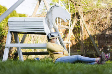 Girl sitting in garden next to wooden horse wearing VR glasses - MOEF02286