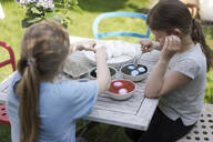 Two girls dyeing Easter eggs on garden table - MOEF02289