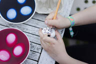 Close-up of girl painting face on Easter egg on garden table - MOEF02295