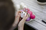Close-up of girl decorating Easter egg on garden table - MOEF02301