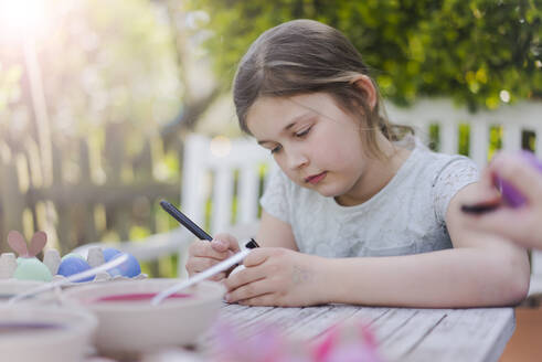 Girl painting Easter egg on garden table - MOEF02304