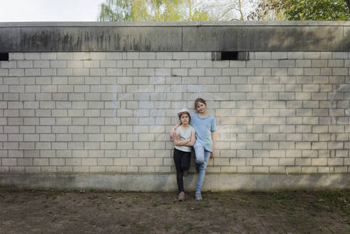 Portrait of two girls standing at a brick wall - MOEF02307