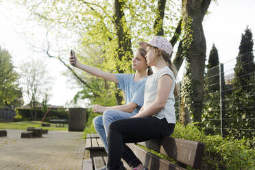 Two girls sitting on a park bench taking a selfie - MOEF02310