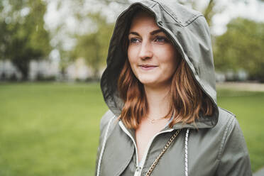 Young woman wearing hooded jacket on a rainy day - FBAF00775
