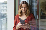 Young woman using cell phone at the balcony door - FBAF00796