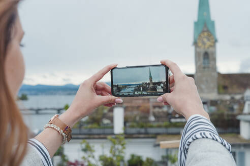 Young woman taking smartphone picture in the city, Zurich, Switzerland - FBAF00805