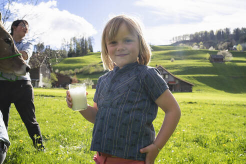 Portrait of smiling girl holding a glass of fresh milk on pasture - FBAF00844