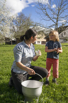 Mother and daughter with fresh milk in a bucket on pasture - FBAF00850
