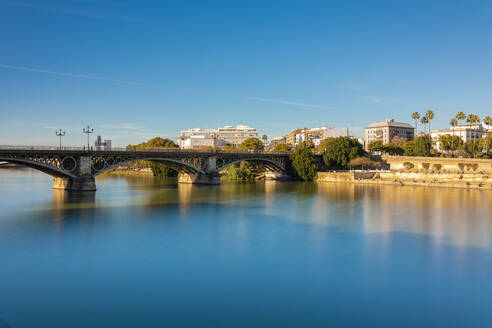 Long exposure of Puente de Triana on Guadalquivir River with Seville in the background - TAMF01569