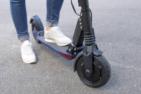 junge Frau mit e - scooter, Elektroroller, Roller, Elektro-Mobilität, Umweltschutz, lifestyle, Berlin, Deutschland - BFRF02027