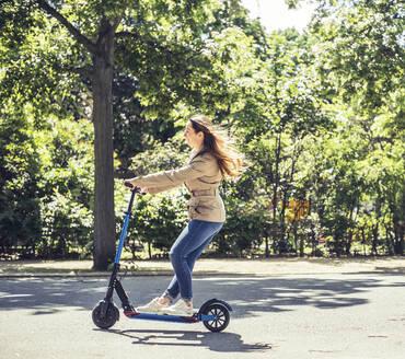 junge Frau mit e - scooter, Elektroroller, Roller, Elektro-Mobilität, Umweltschutz, lifestyle, Berlin, Deutschland - BFRF02030