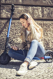 Happy woman sitting on E-Scooter listening music with headphones and smartphone - BFRF02039