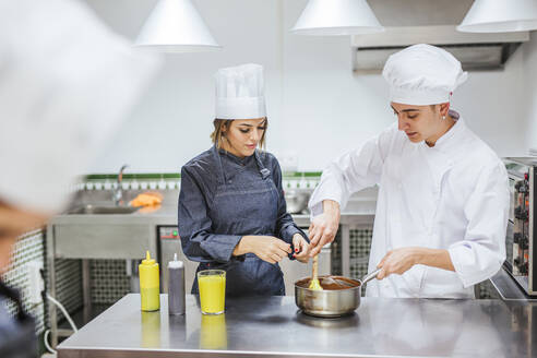 Junior chefs stirring chocolate sauce - LJF00154