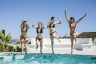 Young women enjoying the summer time at pool, jumping into the water - LJF00250