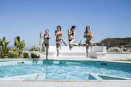 Young women enjoying the summer time at pool, jumping into the water - LJF00253