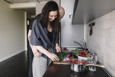 Man watching woman preparing salad in the kitchen - EYAF00264