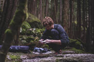 Climber taping fingers before bouldering in forest, Squamish, Canada - ISF21923