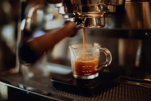 Barista pouring fresh coffee into measuring jug on coffee machine in cafe, shallow focus - ISF22079