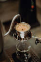 Boiled kettle water pouring into coffee filter on cafe counter, close up shallow focus - ISF22094
