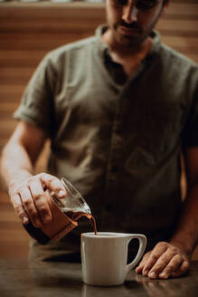 Barista pouring fresh black coffee into mug on cafe counter, shallow focus - ISF22097