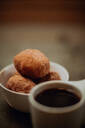 Cup of black coffee and bowl of doughnuts on cafe table, close up shallow focus - ISF22100