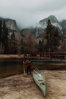 Young female canoeist looking out from riverbank, rear view, Yosemite Village, California, USA - ISF22103