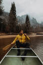 Young male canoeist rowing canoe on river, Yosemite Village, California, USA - ISF22106