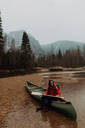 Young female canoeist sitting on canoe in river, Yosemite Village, California, USA - ISF22109