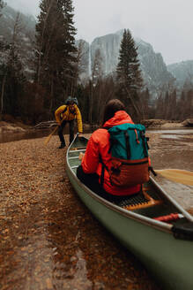Young canoeing couple pushing off from riverbank, Yosemite Village, California, USA - ISF22112