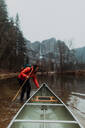 Young female canoeist pulling canoe in river, Yosemite Village, California, USA - ISF22115