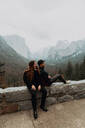 Young couple sitting on wall in mountain landscape, Yosemite Village, California, USA - ISF22136