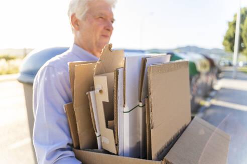 Senior man recycling cardboard carrying cardboard box - AFVF03450