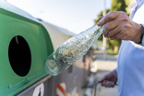 Close-up of man putting bottle into bottle bank - AFVF03456