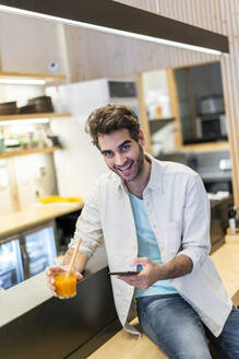 Portrait of a laughing man with cell phone sitting at the counter of a bar having a drink - AFVF03494