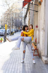 Carefree young woman carrying friend in the city - AFVF03530