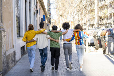 Rear view of group of friends walking arm in arm in the city - AFVF03533