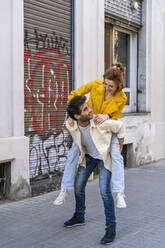 Man giving girlfriend a piggyback ride on pavement in the city - AFVF03536