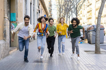 Happy group of friends having fun in the city running on pavement - AFVF03548
