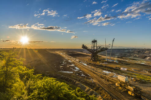 High angle view of bucket-wheel excavator at mine against sky during sunset - FR00854