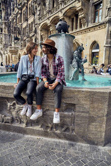 Young couple sitting at fountain - SUF00579