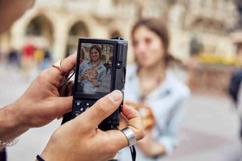 Young couple taking a photo, woman with brezel in Munich, Germany - SUF00585