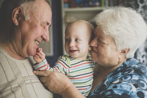 Happy grandparents holding their baby grandson - IHF00160