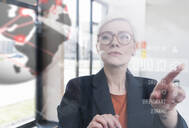 Businesswoman touching glass wall with data in office - UUF17906