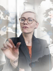 Businesswoman touching virtual glass wall in office - UUF17909