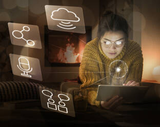 Young woman using tablet at home surrounded by internet symbols - UUF17912