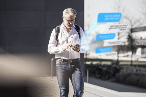 Mature businessman using cell phone for messaging in the city - UUF17915